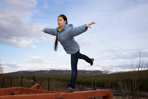girl doing gymnastic element of balance on one leg on the balance beam
