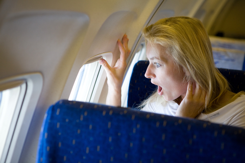 Surprised woman looking out airplane window.