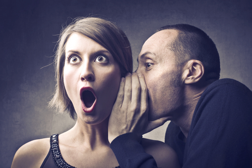 Man telling an astonished woman a gossip